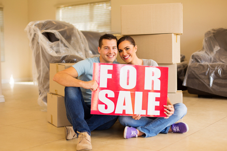 sale sign: moving couple holding for sale sign at home