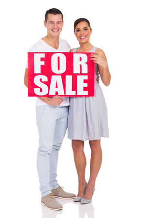 for sale sign: portrait of couple holding a for sale sign on white background