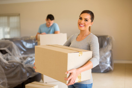 lovely: couple carrying boxes moving in new house