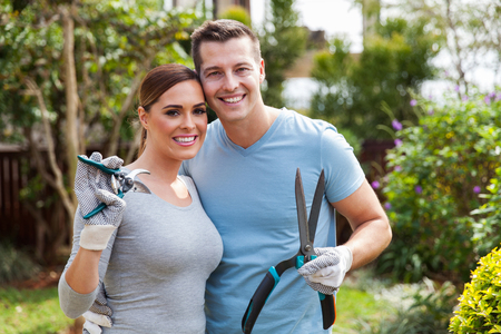 man at work: lovely couple holding gardening tools in home backyard