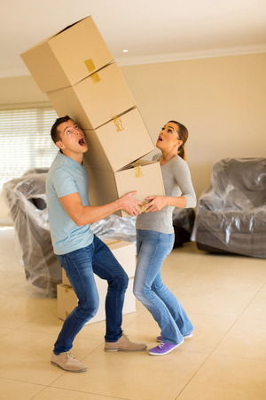 screaming young couple with falling stack of boxes Stockfoto