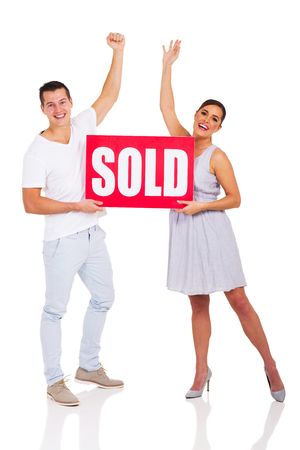 sold sign: excited young couple holding sold sign isolated on white background