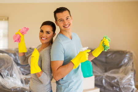 apartment cleaning: cheerful young couple cleaning their new house Stock Photo