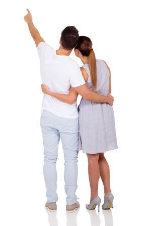 白い背景の上に指している結婚されていたカップルの背面図