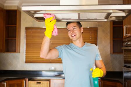 Gelukkig jonge man schoonmaak keuken Stockfoto