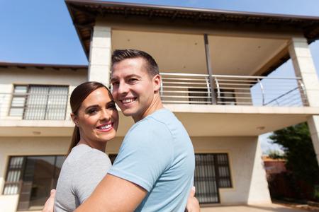 couple souriant regardant en arrière en face de leur maison