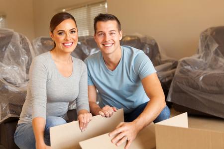 felice giovane coppia disimballaggio scatole e lo spostamento in una nuova casa Archivio Fotografico