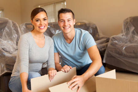 family moving house: happy young couple unpacking boxes and moving into a new home