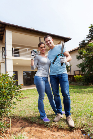women in jeans: happy young couple with gardening tools in front of house Stock Photo