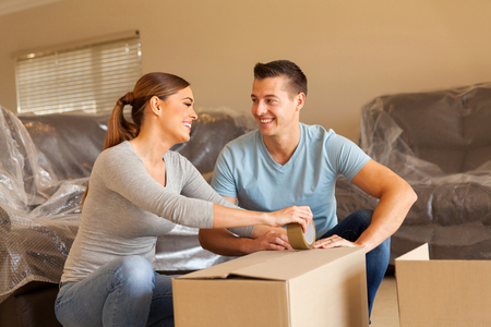 cheerful couple packing for new house