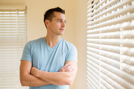 good looking man: thoughtful man with arms crossed at home looking outside