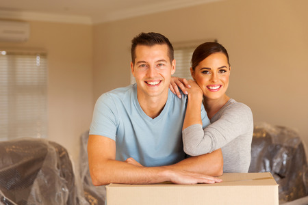 buyer: smiling couple leaning on boxes in new home Stock Photo