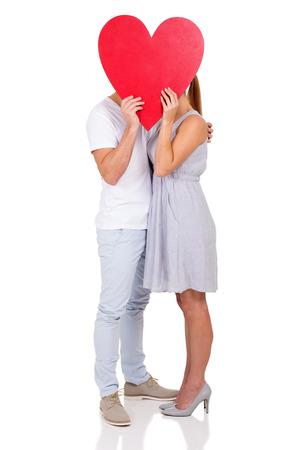 beso: pareja besándose detrás de símbolo del corazón aislado en el fondo blanco