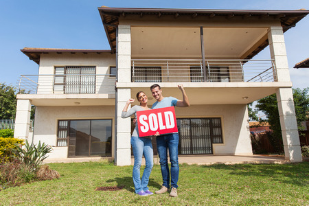 sold sign: happy couple standing outside their house and holding sold sign Stock Photo