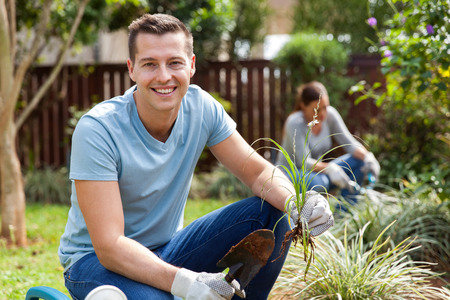 young wife: portrait of good looking young man planting with his wife at home garden Stock Photo