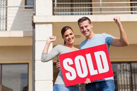 cheerful young couple holding sold sign in front of their old house
