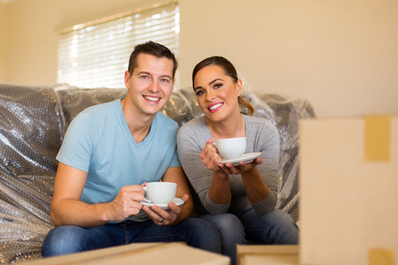moving: happy young couple having coffee break during moving in new home
