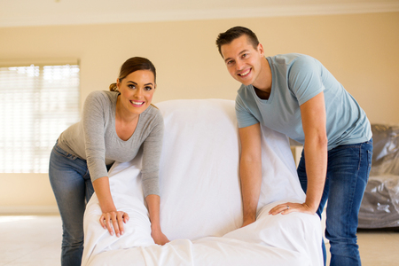 family sofa: happy young couple redecorating their home