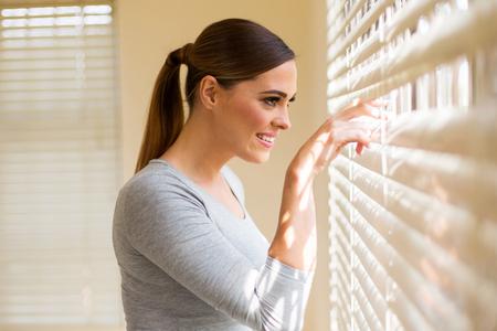 windows: hermosa mujer mirando a través de persianas de la ventana Foto de archivo