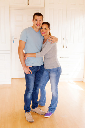 couples in love: portrait of cute couple embracing in their new home