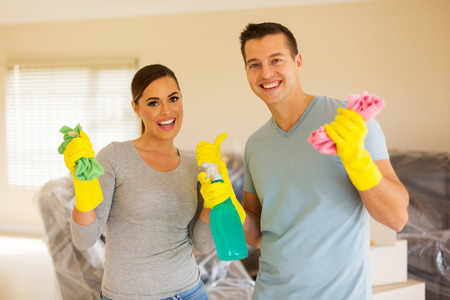 house chores: portrait of young couple cleaning their new house Stock Photo