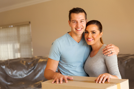 portrait of happy husband and wife moving in new home