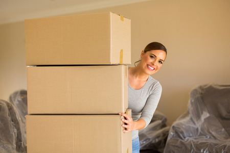 buyer: excited woman standing behind cardboard boxes in new home