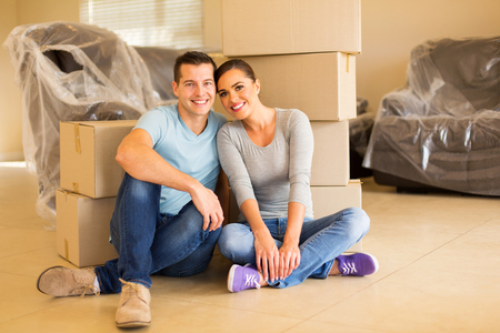 people sitting: portrait of happy couple sitting in new house