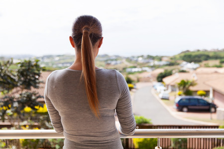 view girl: rear view of young woman standing on balcony at home