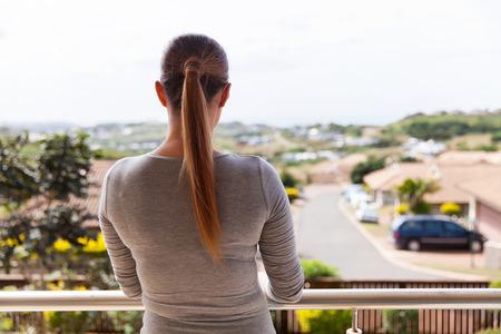 mujeres de espalda: Vista posterior de la mujer joven de pie en el balcón en el hogar