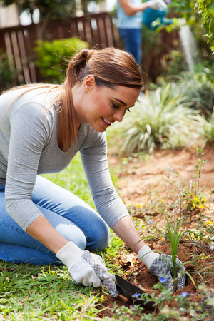 home and garden: happy young woman planting in home garden Stock Photo