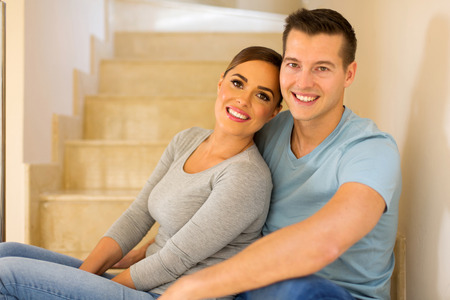 inside house: relaxed young couple sitting on stairs in new house