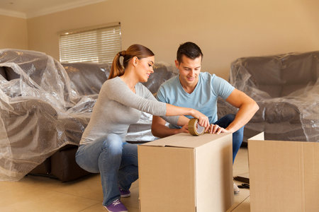 cardboard house: couple sealing moving boxes in their old home Stock Photo