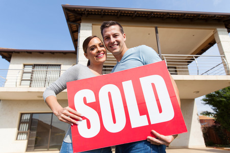lovely young couple with sold sign in front of their old house