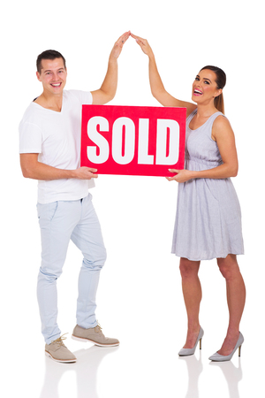 sold sign: cheerful couple holding sold sign for house