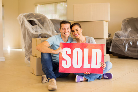sold sign: beautiful couple holding sold sign surrounded by cardboard boxes