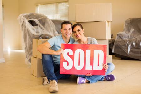 schönes Paar verkauft Zeichen von Kartons umgeben halten