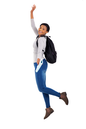 modern girls: cheerful young female african college student jumping on white background