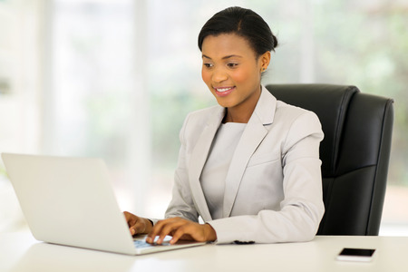 african american woman smiling: professional african corporate worker working on laptop Stock Photo