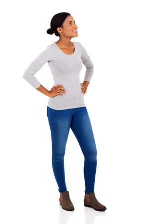 in jeans: La mujer afroamericana alegre mirando hacia arriba sobre fondo blanco