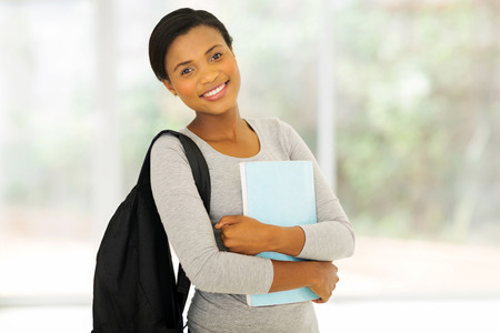 woman standing: portrait of beautiful african college student holding a book Stock Photo