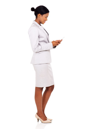 happy african: side view of happy african business woman using cell phone isolated on white
