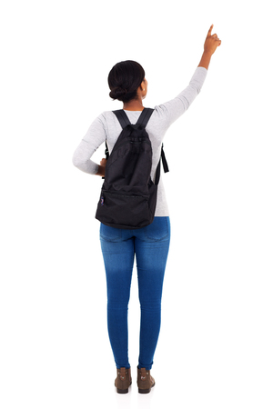 espalda: Vista trasera de la muchacha de universidad africano se�alando el espacio vac�o en el fondo blanco