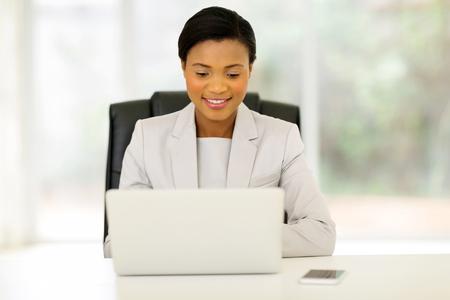 personas sentadas: bastante joven ejecutivo de negocios africano usando la computadora port�til en la oficina