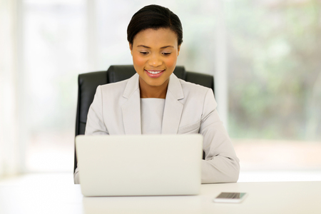 charming business lady: pretty young african business executive using laptop in office