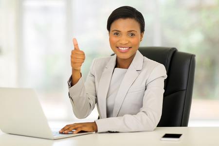 mujer trabajadora: alegre africano ejecutivo de negocios americano que da el pulgar para arriba en la oficina