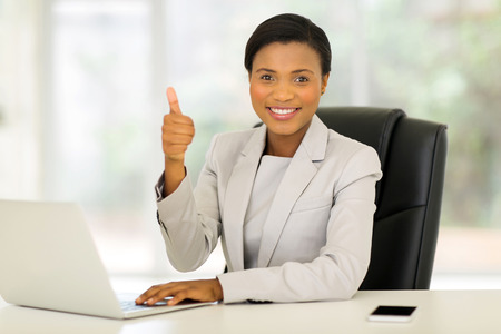 charming woman: cheerful african american business executive giving thumb up in office