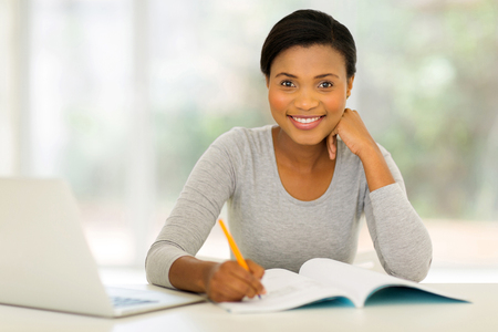 african student: beautiful afro american woman studying at home