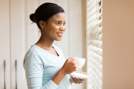 woman window: attractive african woman drinking coffee near the window at home Stock Photo