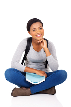 students studying: happy african female college student sitting on white background Stock Photo